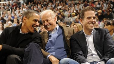Barack Obama, Joe Biden and Hunter Biden talk during a college basketball game in 2010.