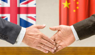 Two male hands reaching out to shake in front of a British flag on the left and a Chinese flag on the right