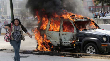 A woman walks past a traffic patrol vehicle set ablaze by angry demonstrators during a protest demanding justice and clarification for the disappearance of 43 students from Ayotzinapa, in Chi