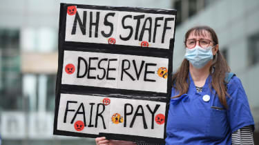 Nurse protesting with placard reading 'NHS staff deserve fair pay'