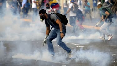 Venezuelan anti-government students protect from tear gas shot by riot police during a protest, in Caracas on February 19, 2014. Four people have been killed in violence linked to the protest