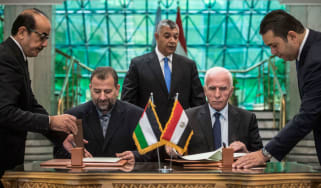 Fatah's Azzam al-Ahmad (right) and Saleh al-Aruri (left) of Hamas sign the reconciliation deal