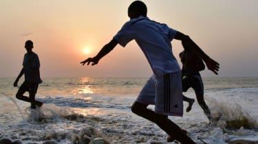 Boys play football on a beach in Gabon