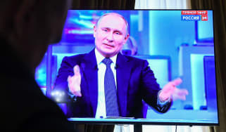 Journalists watch a live broadcast of Vladimir Putin's annual televised phone-in with the nation