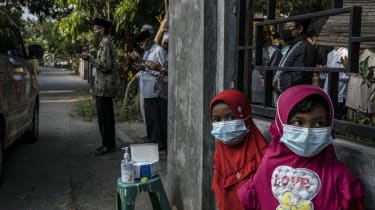 Two children stand as their relatives pray by an ambulance in Yogyakarta, Indonesia