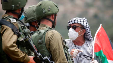 A Palestinian protester confronts Israeli forces
