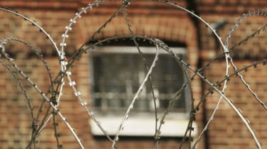 The window of a cell at Norwich Prison is seen through coils of razor wire