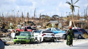 A woman walks by destroyed cars in Bahamian neighbourhood