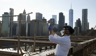 NEW YORK, NEW YORK - APRIL 28:A man takes a photograph on the Brooklyn Bridge during the coronavirus pandemic on April 28, 2020 in New York City. COVID-19 has spread to most countries around