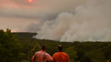 TOPSHOT - Residents watch a large bushfire as seen from Bargo, 150km southwest of Sydney, on December 19, 2019. - A state of emergency was declared in Australia's most populated region on Dec