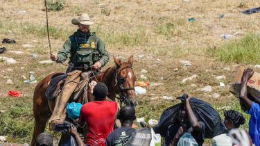 A United States Border Patrol agent on horseback tries to stop Haitian migrants from entering an encampment