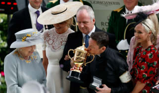 Queen Elizabeth II watches on as Italian jockey Frankie Dettori kisses the Gold Cup at Royal Ascot