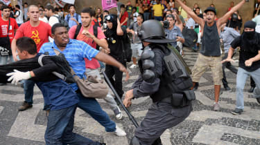 A member of the Special Police Operations Battalion (BOPE) clashes with demonstrators who entered the train's Central Station in Rio de Janeiro, during a protest against a hike on bus fare, o