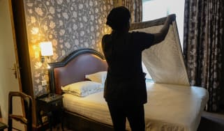 Hotel staff member changing bed sheets