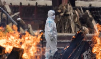 A man in PPE looks on as funeral pyres burn