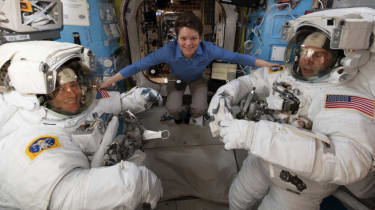 Christina H. Koch (centre) helps Nasa colleagues Anne McClain (left) and Nick Hague (right) ahead of their 22 March spacewalk