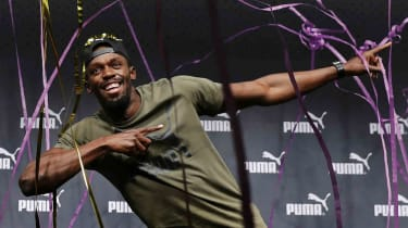 Usain Bolt strikes a familiar pose at a press conference ahead of his final race