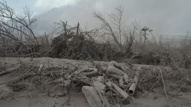 The body of a victim is covered with volcanic ash at a village in Karo district following eruptions of Mount Sinabung volcano, seen in the background, located in Indonesia's Sumatra island on