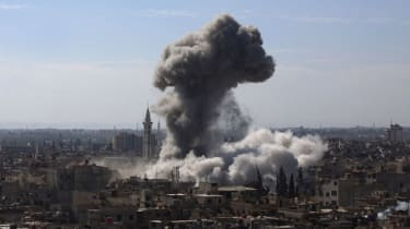 A cloud of smoke rises following an air strike by Syrian government forces in the rebel-held area of Douma