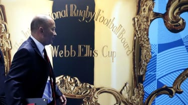 England head coach Eddie Jones walks past a picture of the Webb Ellis Cup