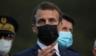 Emmanuel Macron addresses journalists wearing a black face mask/