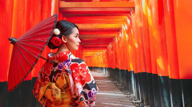Woman wearing a patterned kimono and carrying a parasol. In the background are the red gates at Kyoto's Fushimi Inari-taisha shrine.