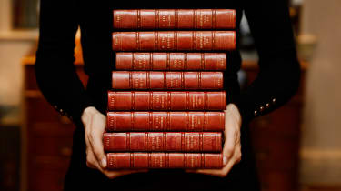 A person carrying a stack of leather-bound books