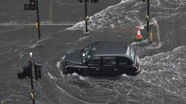 Taxi drives on flooded London street