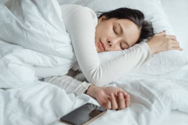 Woman sleeping in bed with smartphone by her side