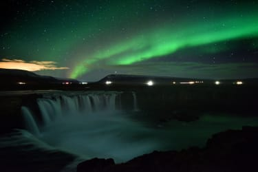 TOPSHOT - The aurora borealis, also known as Northern Lights, is seen over Godafoss waterfall, in the municipality of Thingeyjarsveit, east of Akureyri, in northern Iceland on October 14, 201