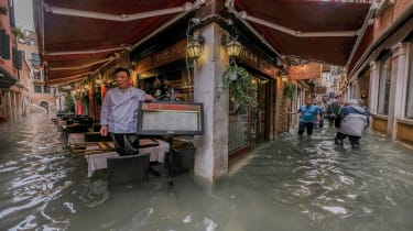 """VENICE, ITALY - OCTOBER 29: A restaurant owner looks at the flood waters on October 29, 2018 in Venice, Italy. Due to the exceptional level of the """"acqua alta"""" or """"High Tide"""" that reached 156"""
