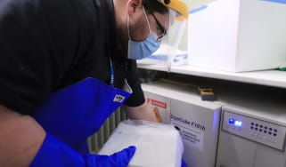 A technician at Croydon Health Services takes delivery of the first batch of Covid-19 vaccinations
