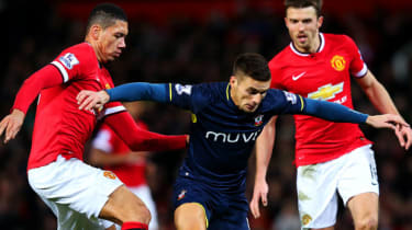 Dusan Tadic of Southampton battles for the ball with Chris Smalling and Michael Carrick of Manchester United