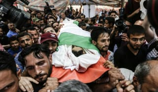 Mourners carry the body of 16-year-old Palestinian Louai Kaheel, who was killed by Israeli airstrikes over the weekend