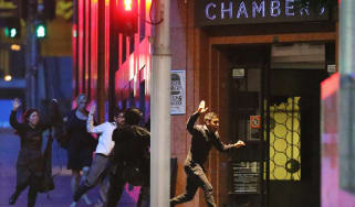 SYDNEY, AUSTRALIA - DECEMBER 15:People run with there hands up from the Lindt Cafe, Martin Place during a hostage standoff on December 15, 2014 in Sydney, Australia.Police stormed the Sydney