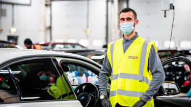 Man in a mask and high-visibility vest standing in front of a car in a warehouse