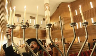 BERLIN, GERMANY - DECEMBER 06:Rabbi Yehuda Teichtal lights a menorah on the sixth day of Hanukkah at the Orthodox synagogue at the Chabad-Lubavitch Jewish Education Center on December 6, 2010
