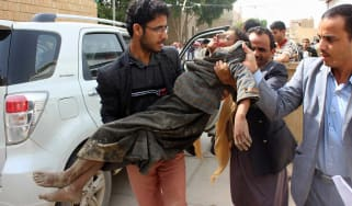 A child is transported to hospital following an airstrike that hit a school bus in Yemen