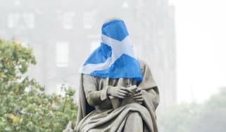 Scotland's Saltire flag draped over a statue of Scottish novelist and playwright Sir Walter Scott in Edinburgh