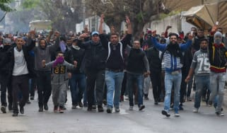 Tunisian protesters gesture towards police