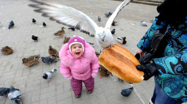 Mother and her child feed birds in the Belarus capital Minsk, on February 6, 2014. AFP PHOTO/ VIKTOR DRACHEV(Photo credit should read VIKTOR DRACHEV/AFP/Getty Images)