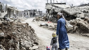 A Kurdish Syrian woman walks with her child past the ruins of the town of Kobane, also known as Ain al-Arab, on March 25, 2015. Islamic State (IS) fighters were driven out of Kobane on Januar