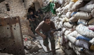 Syrian rebels take cover behind a barricade in Aleppo