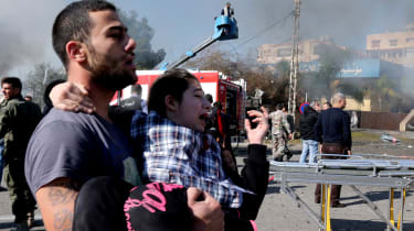 A Lebanese man carries an injured girl following a bomb explosion in a southern suburb of the capital Beirut on February 19, 2014. Twin bomb blasts appeared to target the Iranian cultural cen