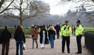 Metropolitan Police officers patrol as people walk in Hyde Park
