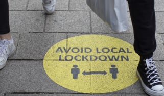 A sign warning people to socially distance to avoid local lockdowns