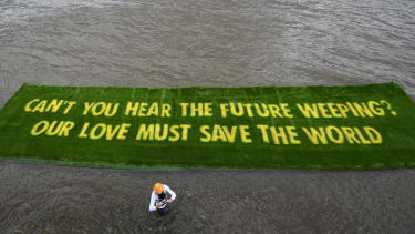 A giant banner grown on a carpet of living grass tells governments to 'act now' in the lead-up to COP26, on 25 June 2021