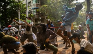 Anti-coup protesters use slingshots against approaching security forces