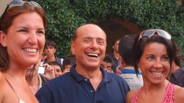 Silvio Berlusconi is photographed with two unidentified women