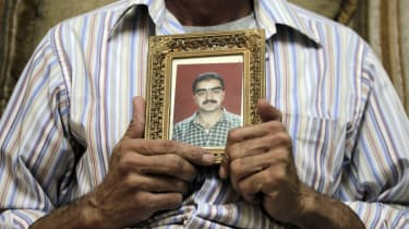 Majdi Fahmi al-Kadumi holds a picture of his brother Bashar, a reporter who disappeared in Aleppo in 2012